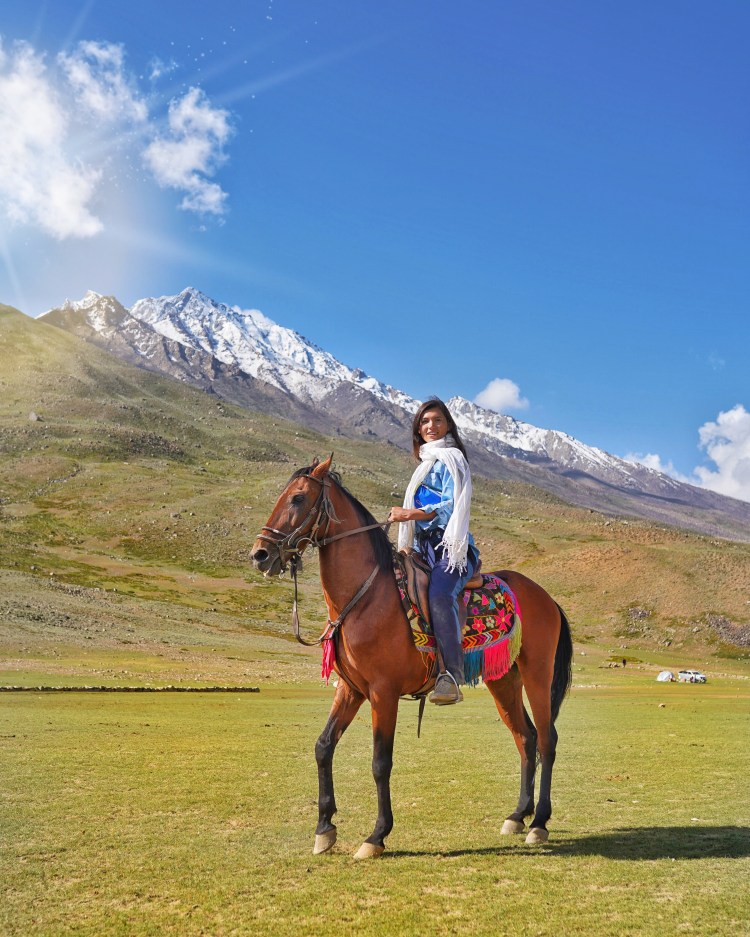 a young woman riding a beautiful horse in Pakistan
