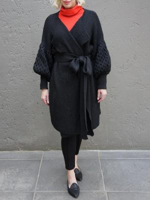 Woman in black knitted cardigan coat with orange polo neck and black pleated pants South Africa