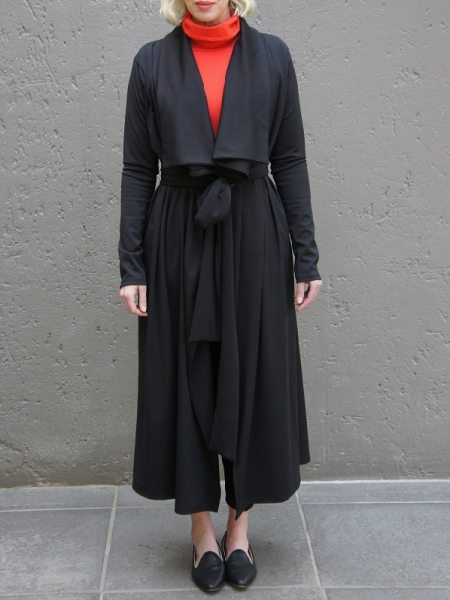 Woman with orange polo neck and black waterfall coat South Africa