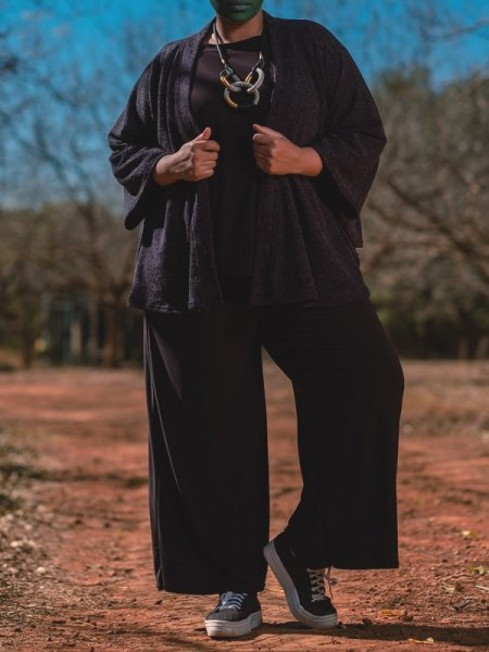 Model in black jumpsuit with navy knitted Cape Jacket South Africa