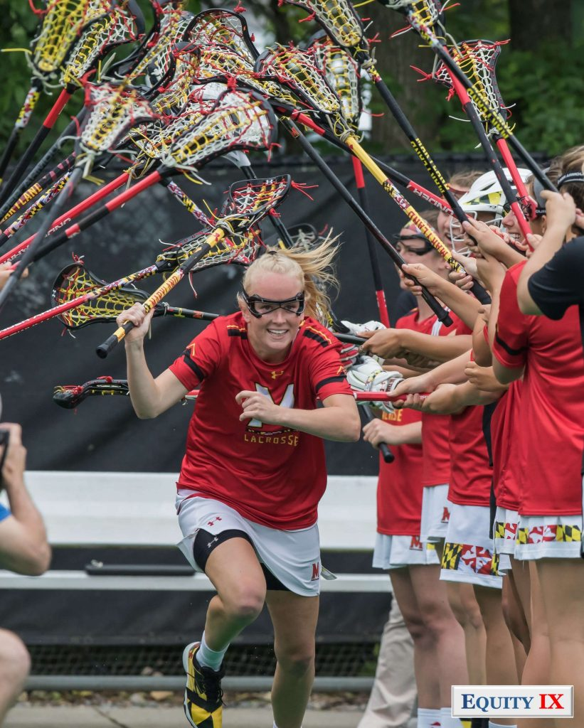 #11 Caroline Steele runs through a line of women's lacrosse sticks at the NCAA Women's Lacrosse Quarterfinals - she has a huge smile on her face with googles and bright red Maryland shirt with matching lacrosse stick © Equity IX - SportsOgram - Leigh Ernst Friestedt