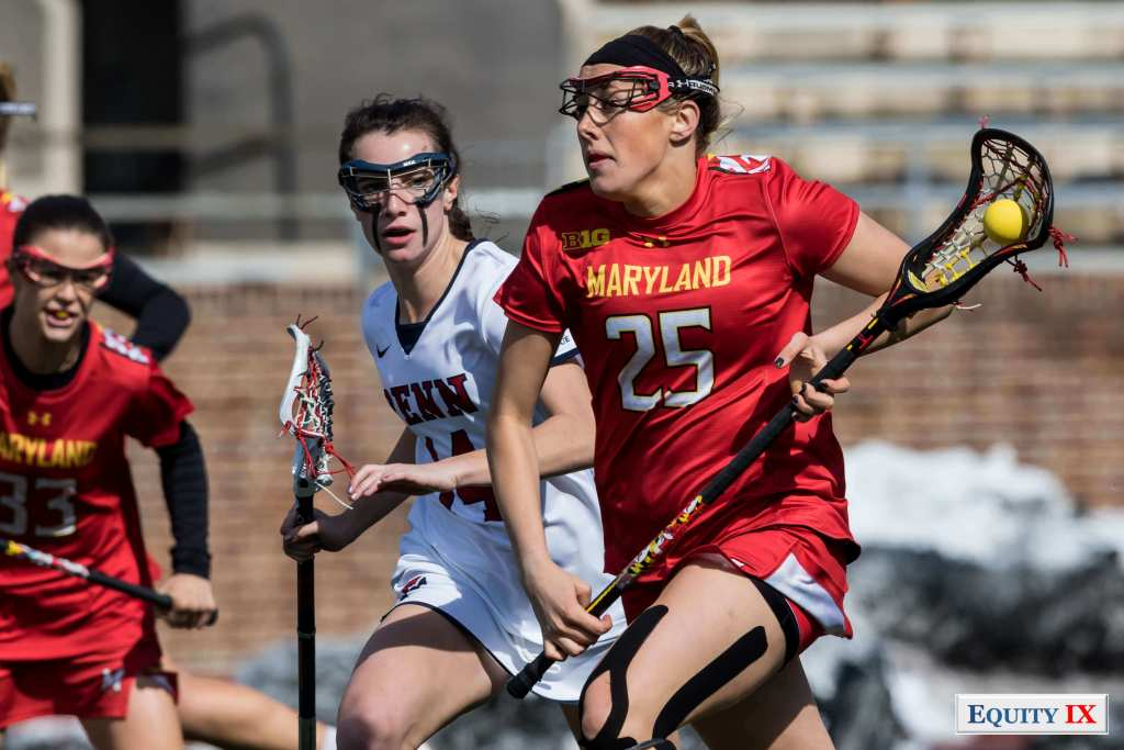 #25 Lizzie Colson (Maryland) breaks ball out of defense wearing bright red Maryland jersey with black headband and red goggles against #14 Zoe Belodeau (Penn) running to catch up © Equity IX - SportsOgram - Leigh Ernst Friestedt