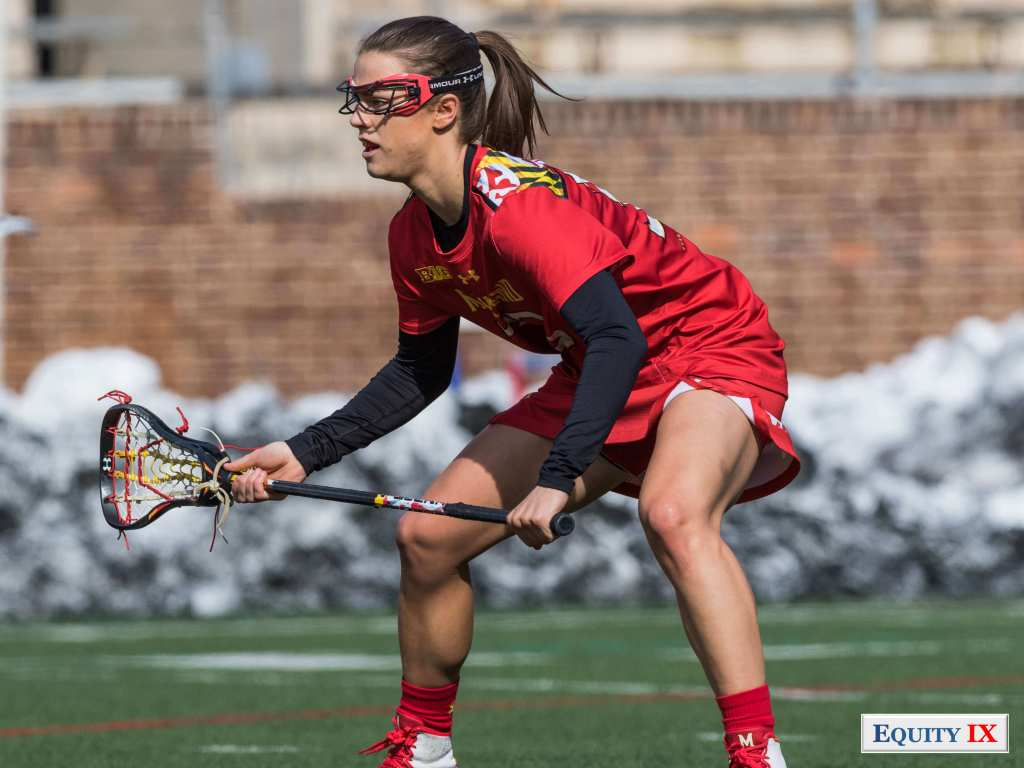 #33 Kathy Rudkin plays defense in bright red Maryland jersey with black lacrosse stick and red goggles crouched down in an athletic stance - 2018 NCAA Women's Lacrosse © Equity IX - SportsOgram - Leigh Ernst Friestedt