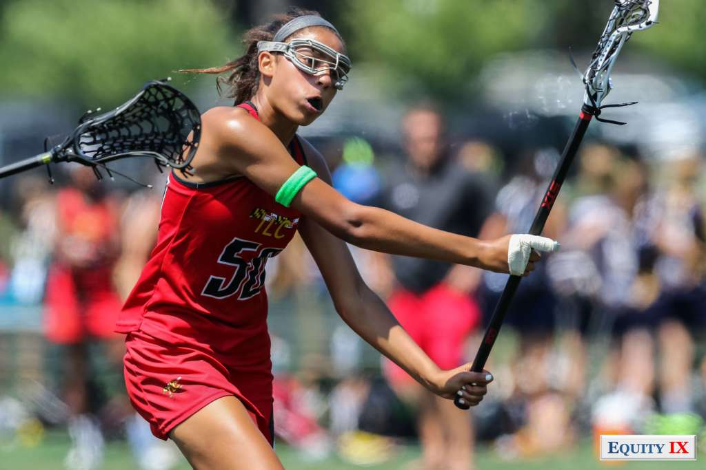 Early Recruit - TLC #50 wearing a red jersey, goggles and green armband to indicate she has committed to play lacrosse in college - shoots the lacrosse ball with an injured index finger © Equity IX - SportsOgram - Leigh Ernst Friestedt