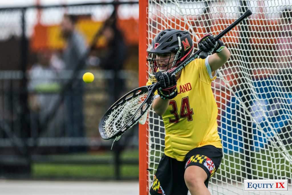 """#34 Megan Taylor - Maryland Women's Lacrosse Goalie stops a shot coming at her oversized Under Armour lacrosse stick with bright yellow jersey and black helmet with red """"M"""" on the side - 2017 NCAA Champions © Equity IX- SportsOgram - Leigh Ernst Friestedt"""