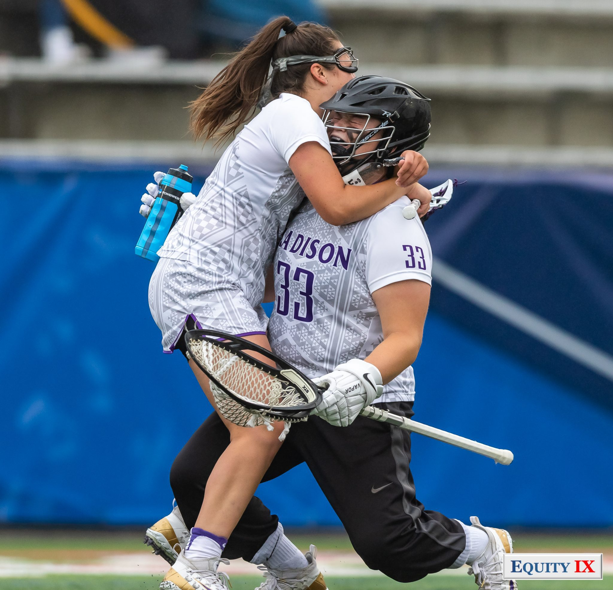 Molly Dougherty (JMU Goalie #33) and Emma Johnson (JMU 31) celebrate by hugging after winning 2018 NCAA Women's Lacrosse Championship - Molly wearing a helmet and carrying oversized goalie stick and blue water bottle © Equity IX - SportsOgram - Leigh Ernst Friestedt