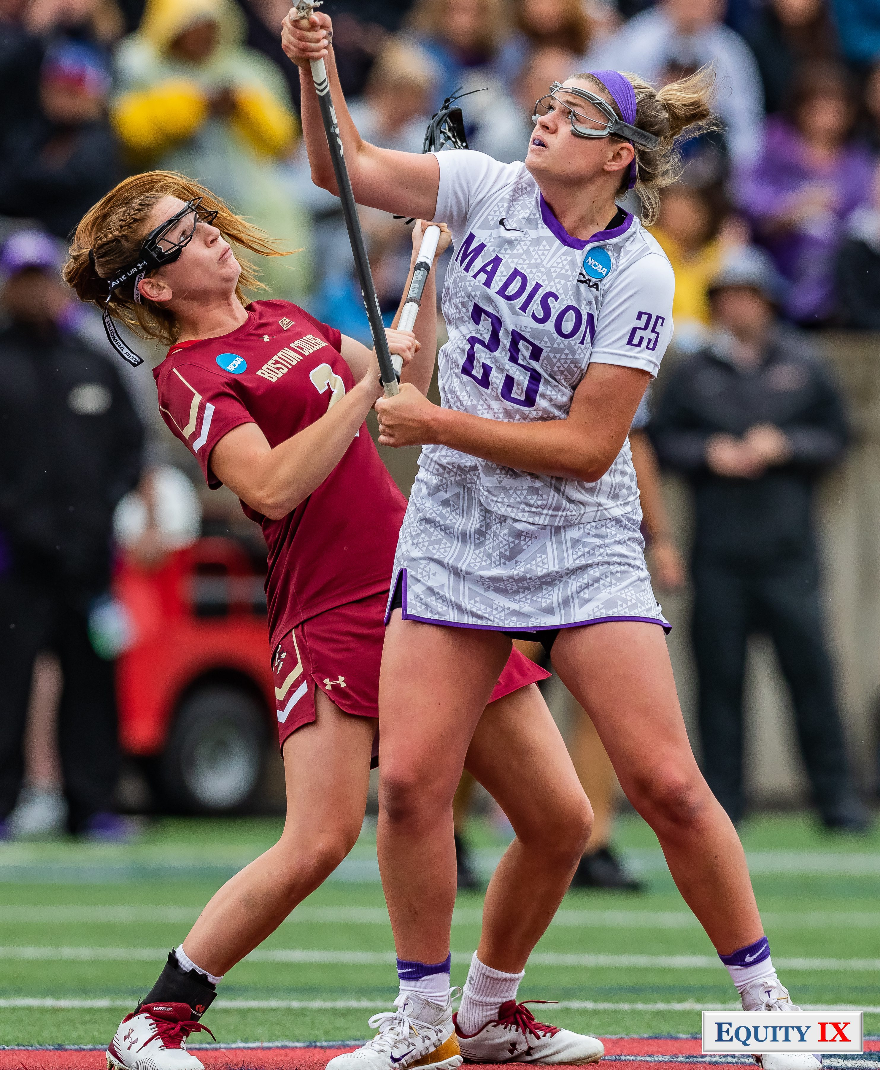 Haley Warden (JMU #25) with purple bandana and goggles draws against Sam Apuzzo (Boston College #2) leaning backwards both are looking up into the air for the ball with their lacrosse sticks drawn to the side - 2018 NCAA Women's Lacrosse Championship Game - Tewaaraton Award © Equity IX - SportsOgram - Leigh Ernst Friestedt