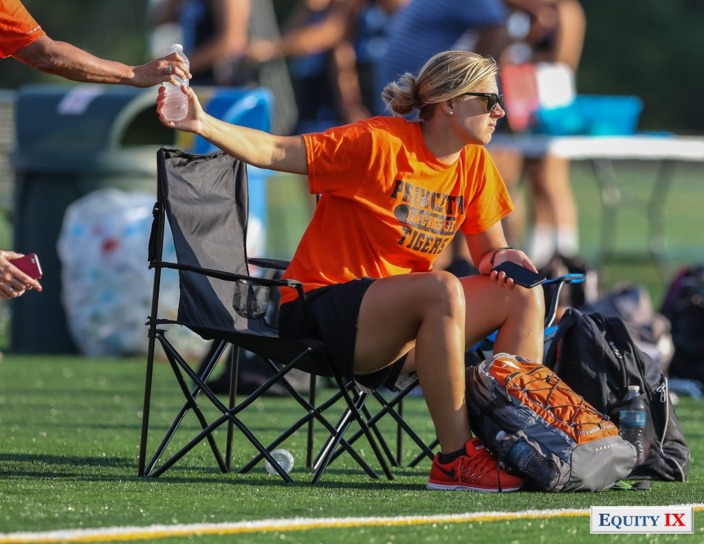 Princeton Women's Lacrosse Coach wearing orange and black Princeton Tigers t-shirt grabs a bottle of water while watching early recruiting at 2015 Nike Elite G8 girls club lacrosse tournament © Equity IX - SportsOgram - Leigh Ernst Friestedt
