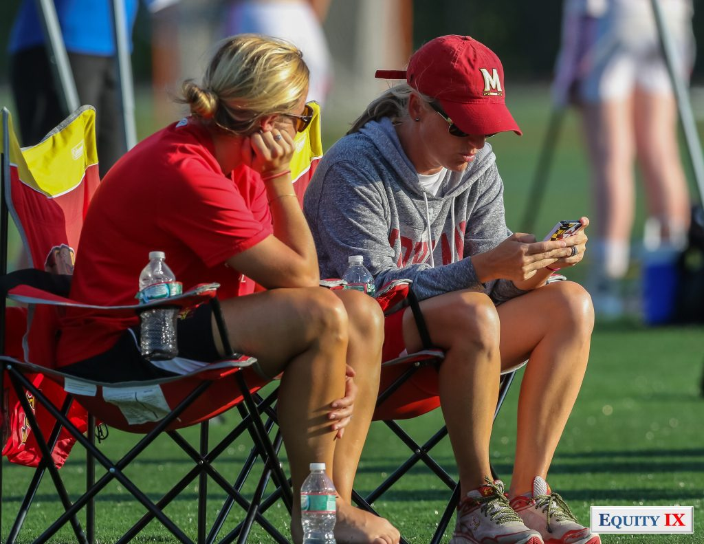 Kathy Reese reads her Maryland cell phone with a red Maryland baseball hat and sunglasses with assistant women's lacrosse coach watching early recruits at 2015 Nike Elite G8 girls club lacrosse tournament © Equity IX - SportsOgram - Leigh Ernst Friestedt