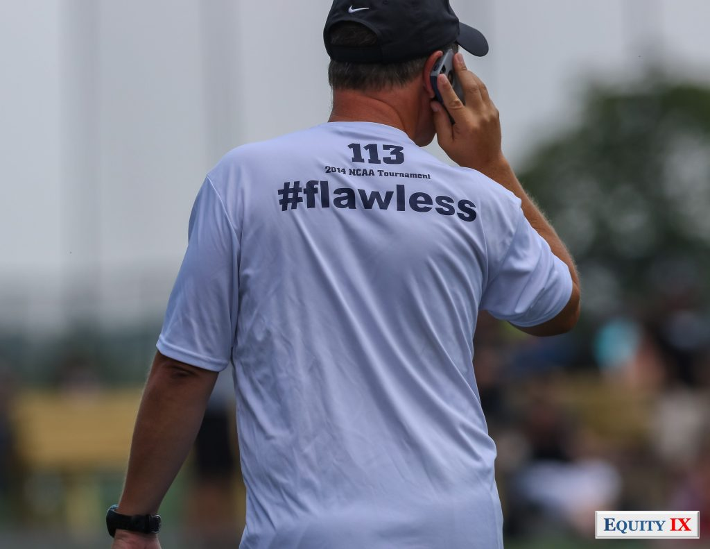 """Ricky Fried - Georgetown Women's Lacrosse Head Coach on the phone at early recruiting girls club lacrosse tournament wearing a """"flawless"""" 2014 NCAA Tournament t-shirt and Nike baseball hat © Equity IX - SportsOgram - Leigh Ernst Friestedt"""