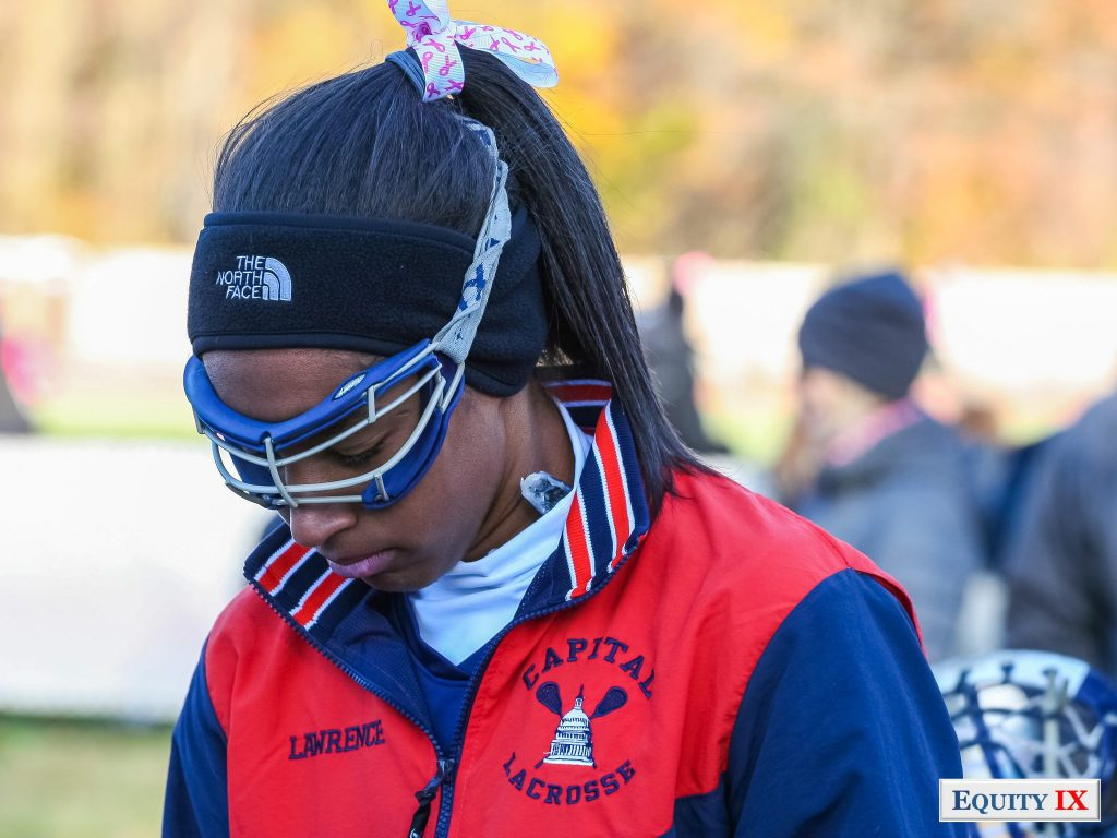 Early Recruit Taylor Lawrence of DC Capital Girls Club Lacrosse committed early to Stanford wearing an orange jacket, goggles, North Face black headband and Lax4Cure bow in her hair - Hotlon-Arms © Equity IX - SportsOgram - Leigh Ernst Friestedt