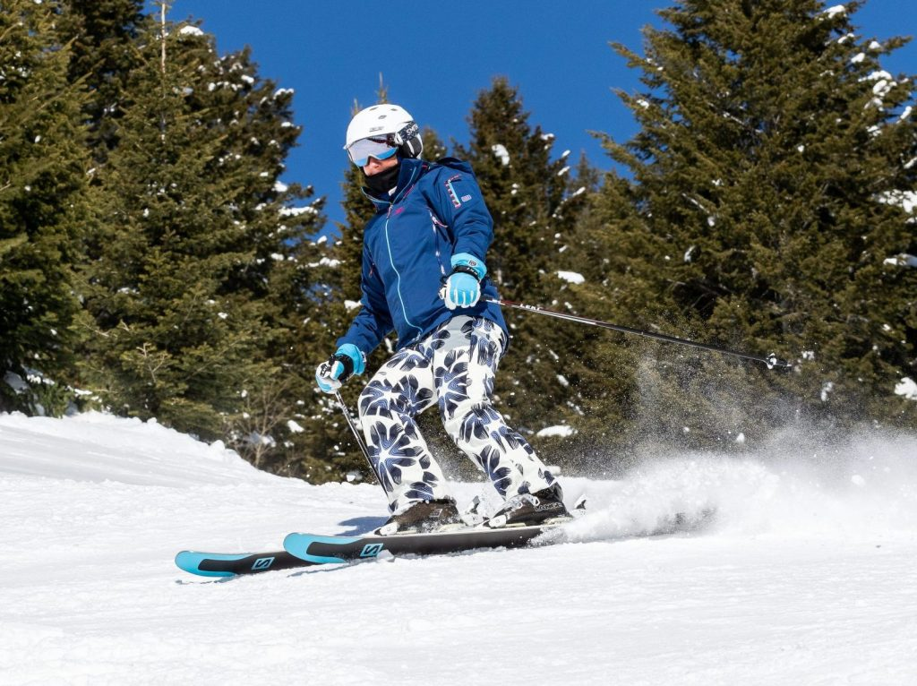 Leigh Ernst Friestedt skiing at Jackson Hole, WY 2018 in blue and white outfit with white helmet and Salomon skis © Equity IX - SportsOgram
