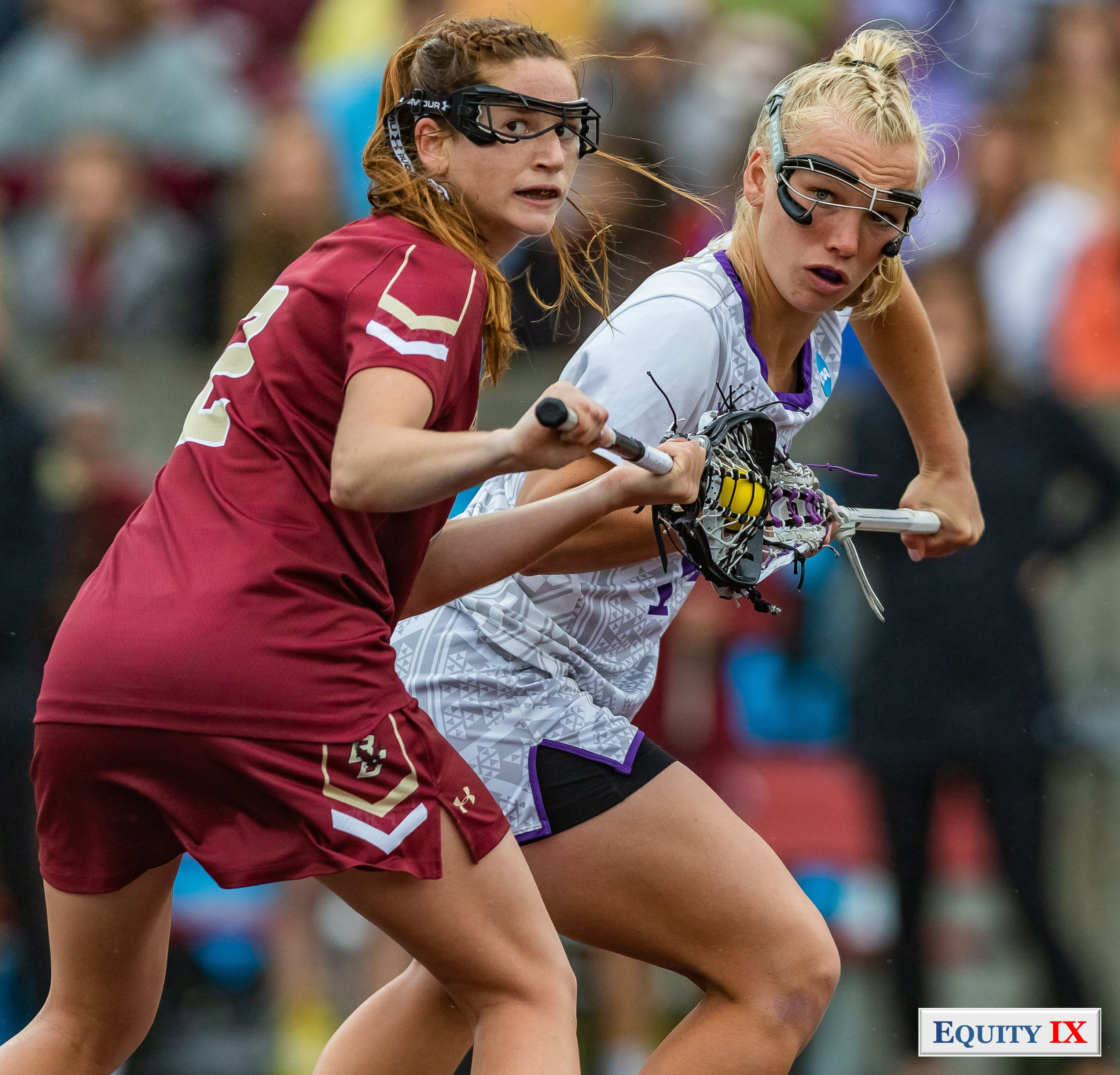 #14 Kristen Gaudian (JMU) with blond hair draws against #2 Sam Apuzzo (Boston College) red jersey both are wearing goggles and looking at the referee waiting to blow the whistle with a yellow lacrosse ball wedged between the lacrosse sticks - 2018 NCAA Women's Lacrosse Championship Game © Equity IX - SportsOgram - Leigh Ernst Friestedt