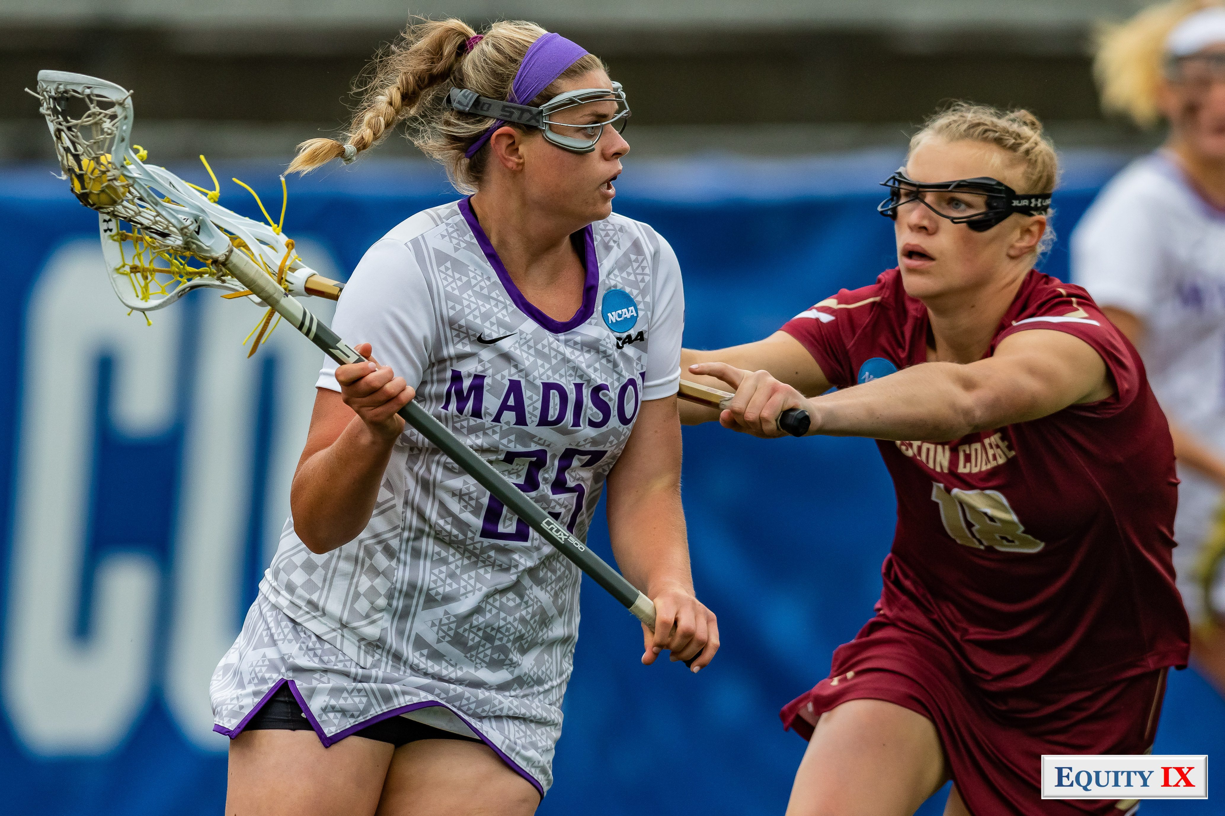 #25 Haley Warden (JUM) cradles yellow lacrosse ball right handed looking to pass wearing purple headband and goggles against #18 Dempsey Arsenault (Boston College) looking into attacker's eyes and cross checking lacrosse stick against JMU's players back - 2018 NCAA Women's Lacrosse Championship Game © Equity IX - SportsOgram - Leigh Ernst Friestedt