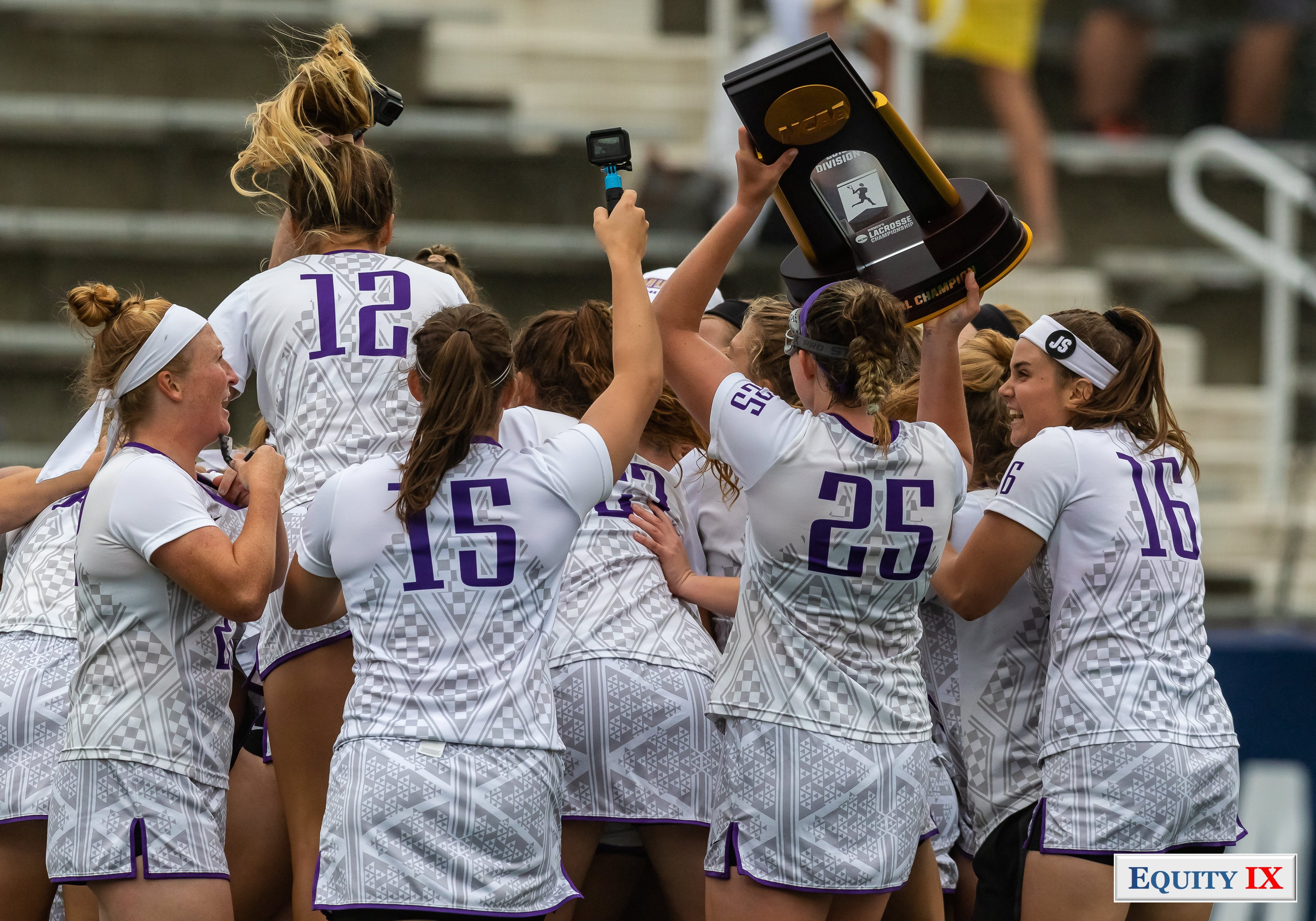 JMU women's lacrosse team celebrate winning national title with #25 Haley Warden raising the NCAA Women's Lacrosse National Champions trophy above head with teammates jumping next to her and holding a small camera to capture the special moment - 2018 NCAA Women's Lacrosse Champions © Equity IX - SportsOgram - Leigh Ernst Friestedt