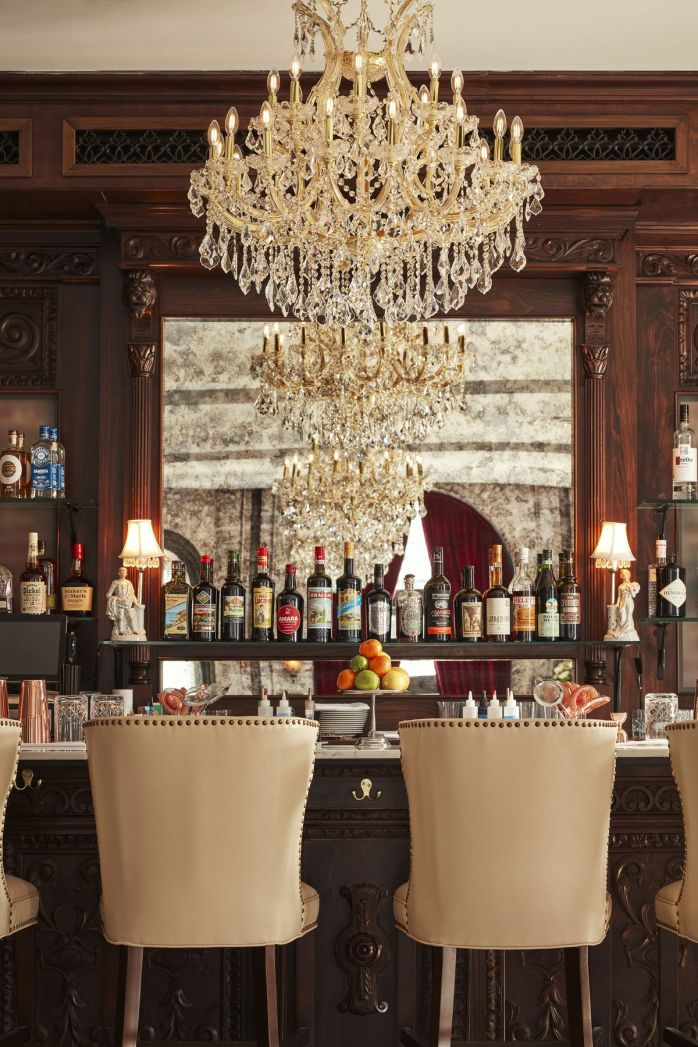 bar with chandelier and seats and mirror behind the bottles