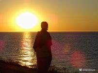 Laura (silhouet) bij de Waddenzee met ondergaande zon
