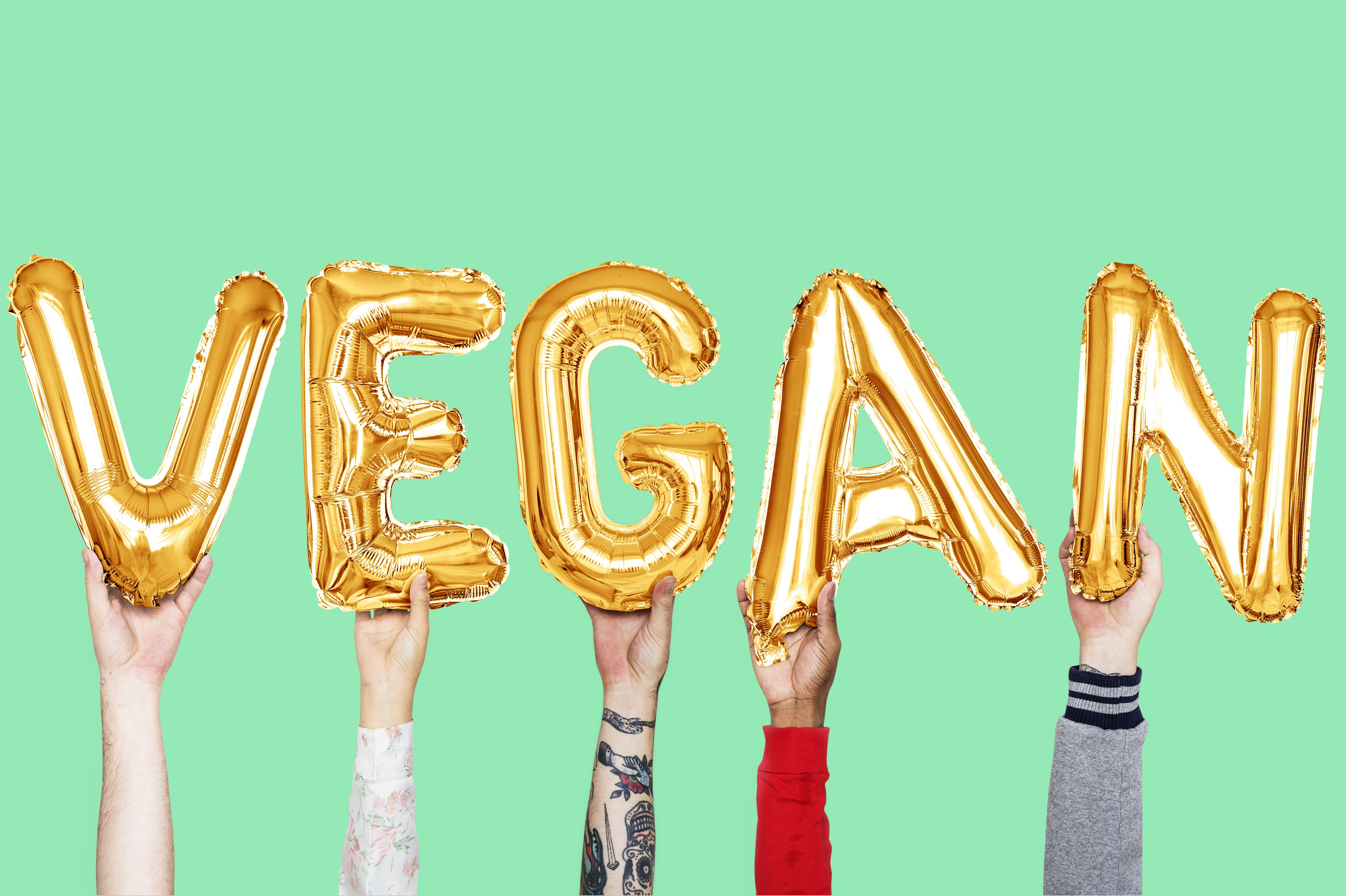 Hands holding vegan word in balloon letters