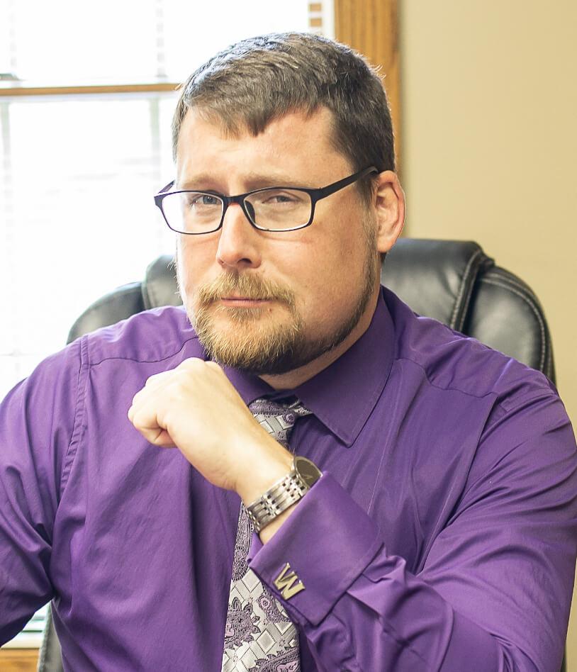 Wesley C. Buchanan in purple shirt looking at camera