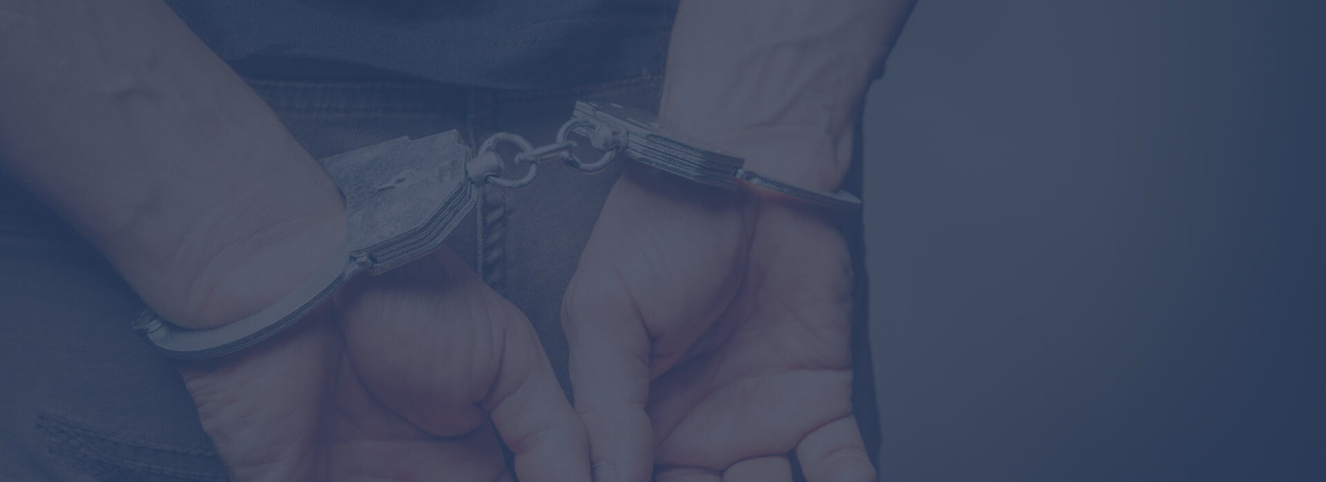 Man's hands close up, handcuffed behind his back