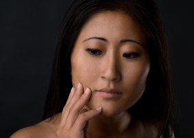 Asian girl with hand on her chin