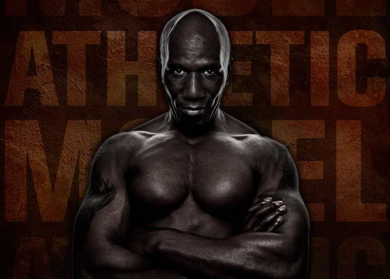 Black muscular man, straight on, serious looking, arms crossed