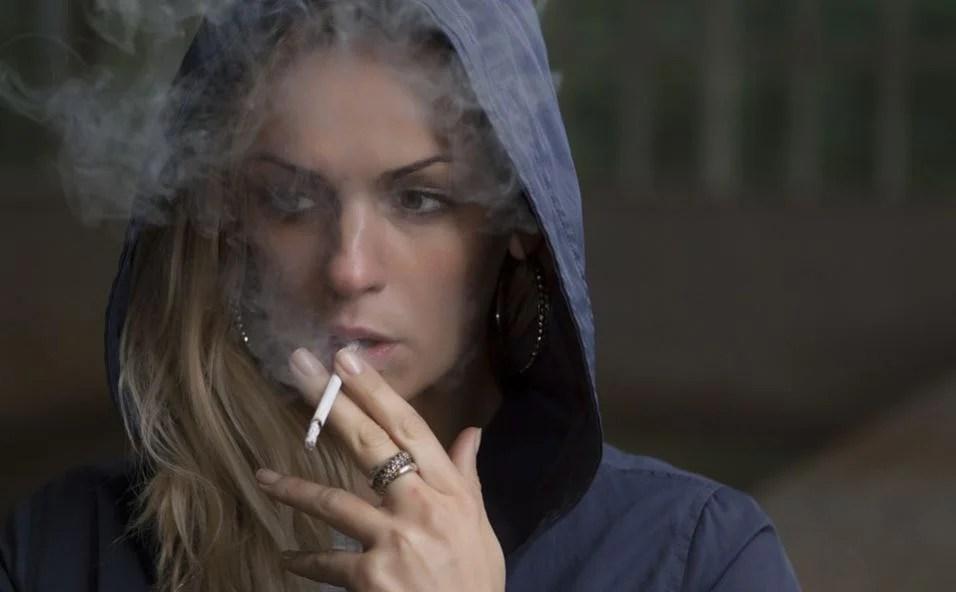 Chica joven fuma con la capucha puesta.