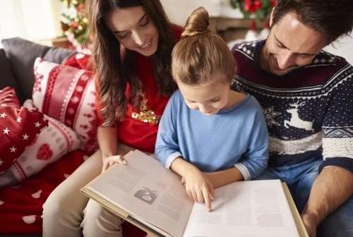 Padre leyendo con su hija algunos cuentos sobre la Navidad para niños.