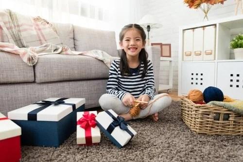 Niña en el salón de casa con varios paquetes de regalos que contienen juguetes solidarios.