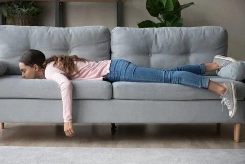 Adolescente tumbada en el sofá sin motivación porque no quiere estudiar.