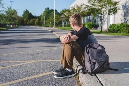 Chico adolescente sentado en el bordillo a la salida de la escuela porque no quiere estudiar.