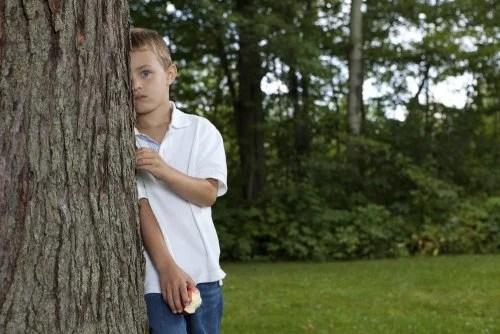 Niño tímido e introvertido escondido detrás de un árbol porque no juega con nadie en el colegio.