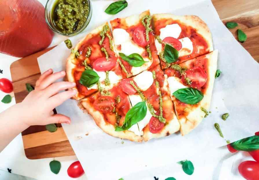 My son's hand reaching for a margherita pizza. The pizza has mozzarella cheese, tomatoes, basil leaves and pesto on it. The pizza is on a piece of parchment paper on a cutting board. This easy margherita pizza recipe is my son's favorite.