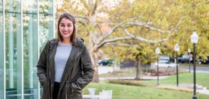 In the photo, a young woman (Erica Corder), wearing an olive coat over a gray shirt, stands and smiles for a posed photo in front of a courtyard with trees.