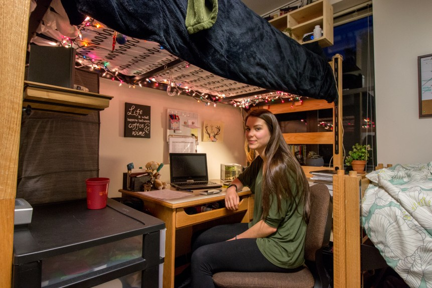 In the photo, a young woman (Emily Barritt) looks toward the camera for a portrait inside of her dorm room. She sits on a computer chair at a desk under a bunked bed, from which hangs multicolored string lights.