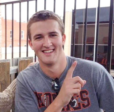 "In the photo, a young man (Colin Moore) smiles and poses for a picture with one hand pointing up toward the sky to indicate number one. He is wearing a gray t-shirt with the word ""Hokies"" written in orange and maroon text."