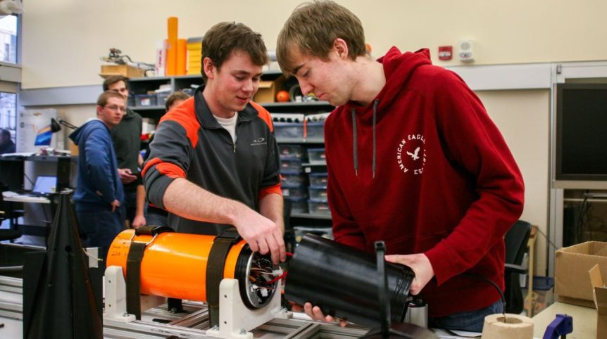Two students are pictured in a lab, putting together pieces of the Javelin shell.