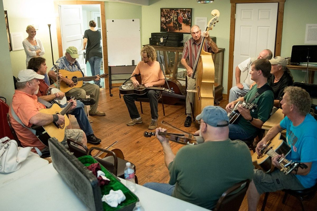 A group of people form a circle with instruments and do a jam session.