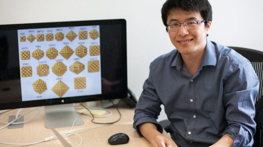 In the photo, a young man, Hongliang Xin, sits at a computer desk with an illustration of polymers pulled up on the computer screen behind him as he smiles toward the camera.