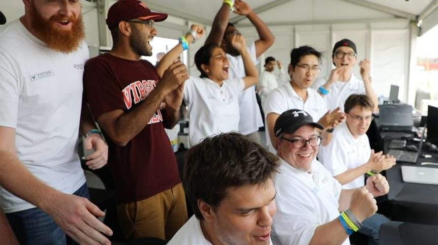 In the photo, a team of people cheer as they look to something out of frame.