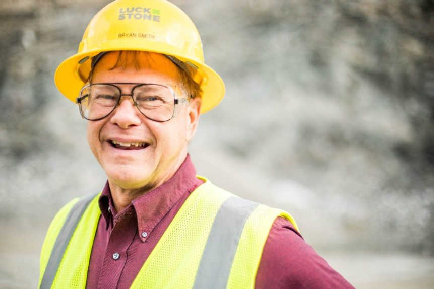A man wearing a yellow hard hat flashes a smile for a photo taken inside a rock quarry.