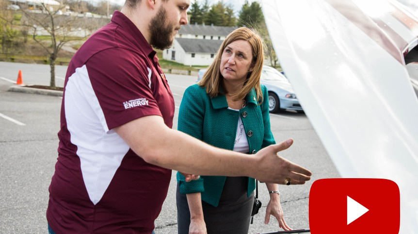 A screenshot of a video still featuring Virginia Tech College of Engineering Dean Julia Ross and a student looking under the hood of a car.