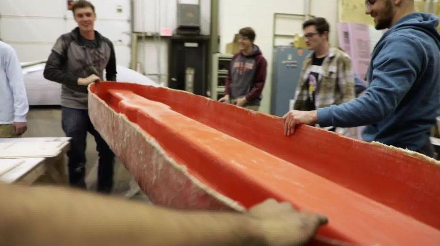 A screenshot of a video still of the Hyperloop team members holding an orange mold in the shape of their Hyperloop pod.