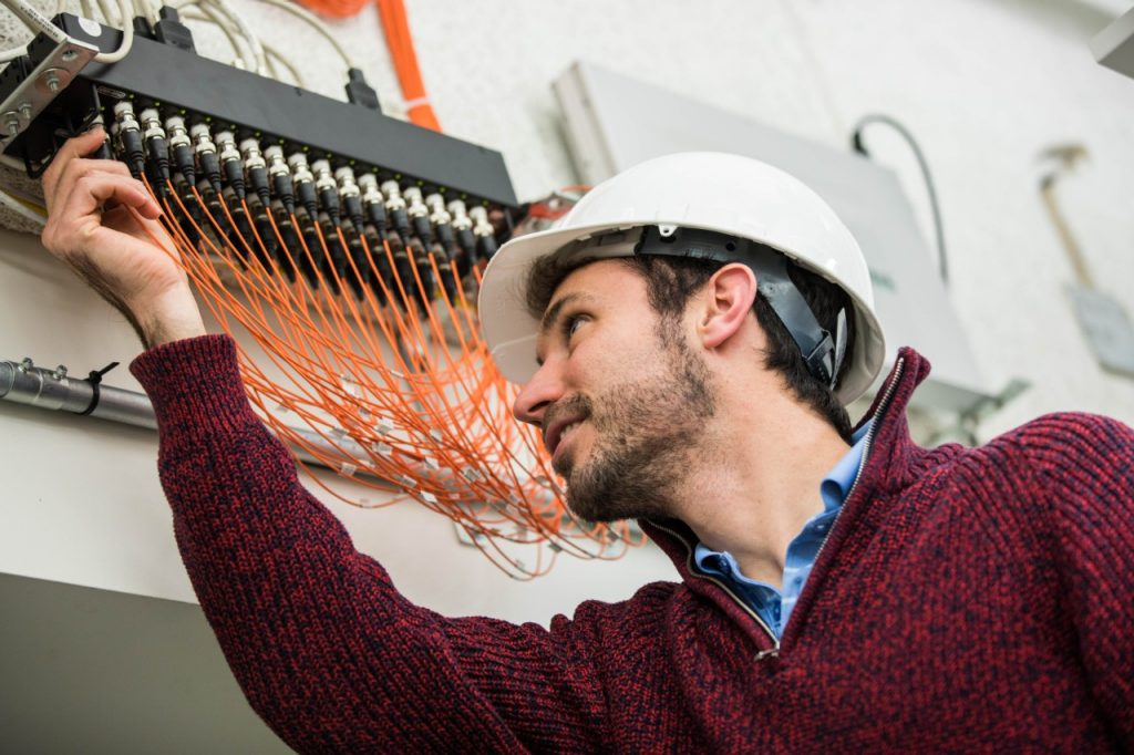 A man wearing a white hard hat and a red sweater reaches toward the ceiling, where he adjusts orange wires linked to a data acquisition system.