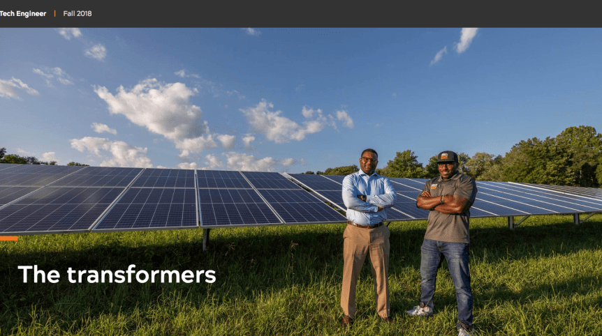 "Screenshot of a photo in which two men pose in front of solar panels in a field. The words ""The transformers"" are written on top of the image."