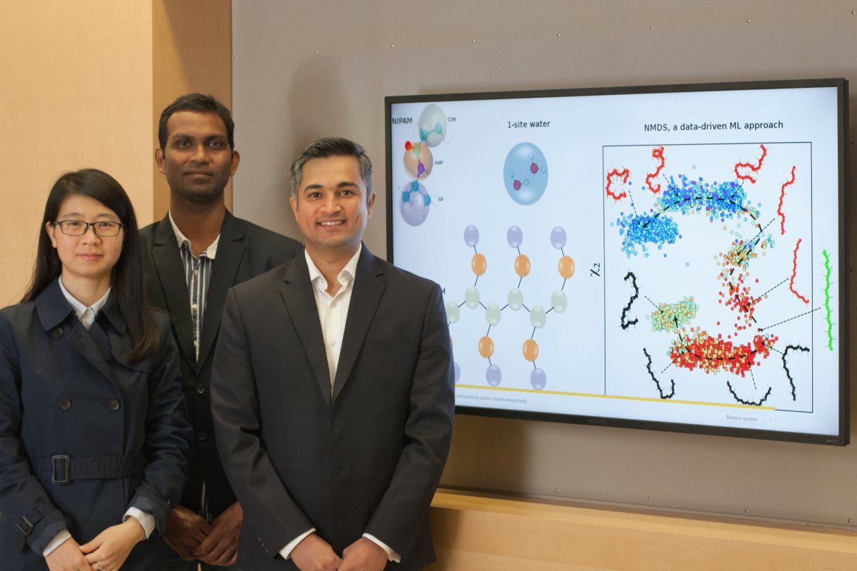Three researchers pose in front of a screen displaying their research.