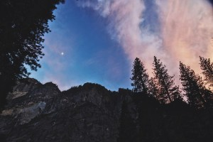 A photo of an evening sky, painted pinks and blues, with a moon shining over a treeline and mountainside.