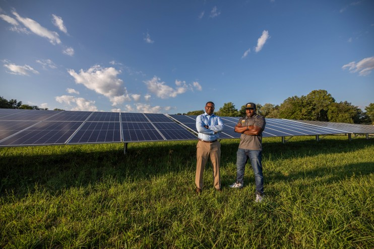 A photo of two men standing with their arms crossed in front of solar panels.