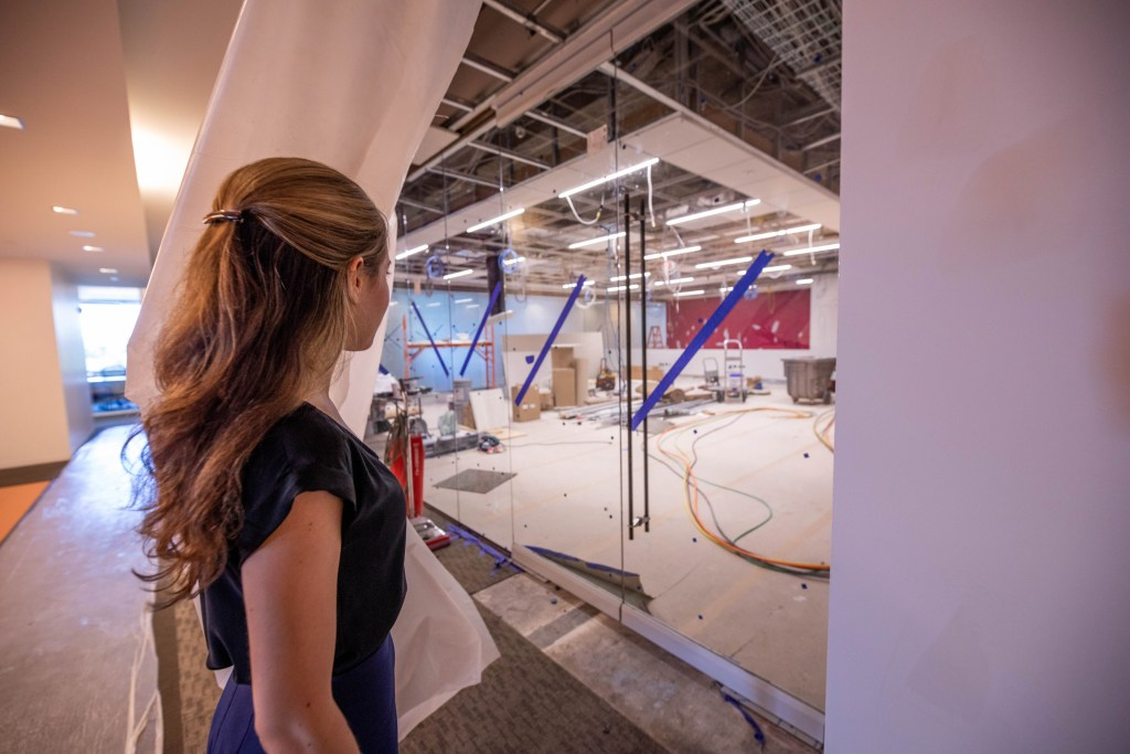 A young woman pulls a curtain back to reveal a lab space under construction.