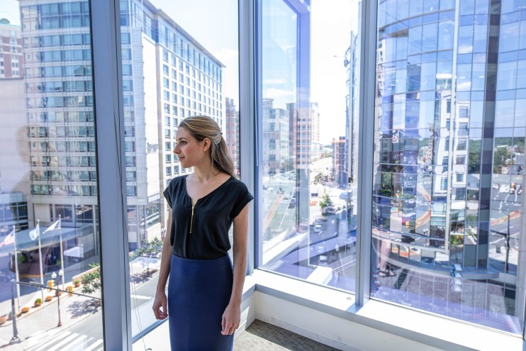 A photo of a young woman staring out windows into a busy cityscape.